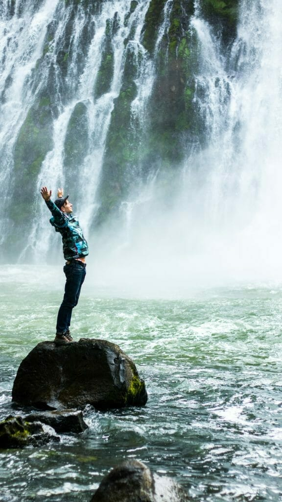 person celebrating near waterfall